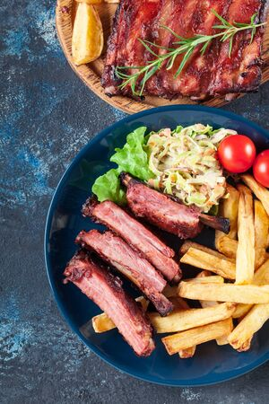 Spicy barbecued pork ribs served with french fries and BBQ sauce