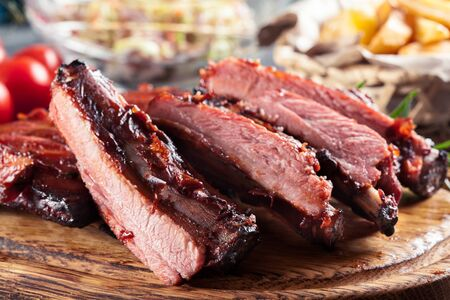 Spicy barbecued pork ribs served with BBQ sauce on chopping board Archivio Fotografico
