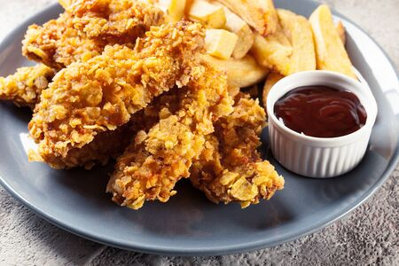 Chicken strips in cornflakes breadcrumb served with french fries