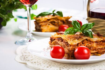 Piece of tasty hot lasagna with red wine. Selective focus Stock Photo