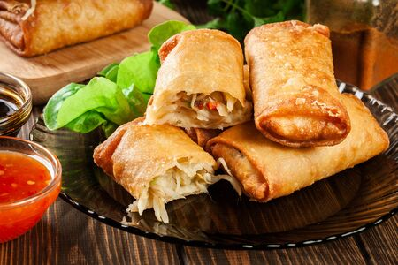 Spring rolls with chicken and vegetables served with sweet chili sauce or soy sauce. Asian cuisine.