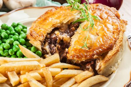 Homemade beef stew pie with french fries. Meat in puff pastry Stock Photo