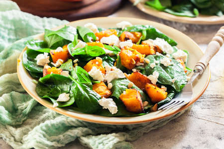 Roasted pumpkin salad with spinach, feta and pine nuts. Autumn dish Imagens