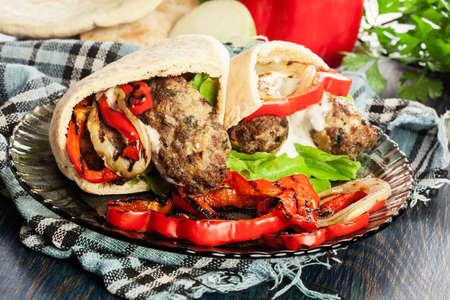 Tasty kofta kebab with grilled paprika and onion served on pita flatbread Stock Photo