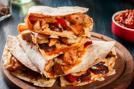 Stack of quesadillas with chicken, sausage chorizo and red pepper served with salsa. Mexican cuisine. Side view