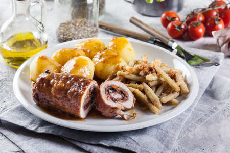 Pork rolls stuffed with vegetables served with potatoes and yellow string beans