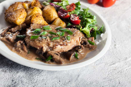 Pork loin chop with mushroom sauce and baked potatoes. Delicious dish