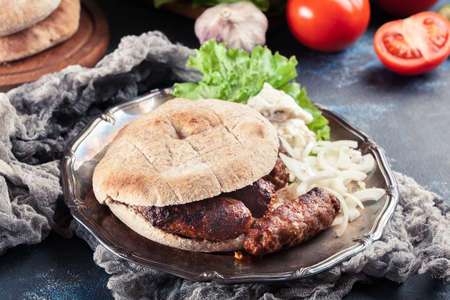 Cevapcici or cevapi served with lepinja bread and onion. Popular dish all over the Balkans Фото со стока