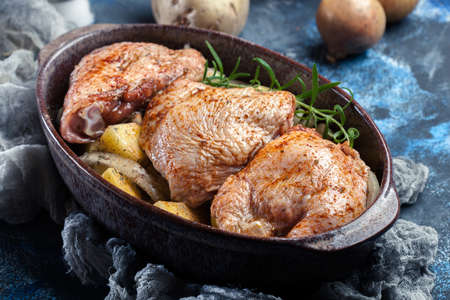 Chicken thighs and potatoes ready for baking in casserole dish