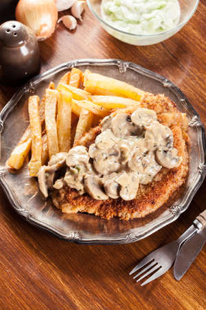 Traditional hunter schnitzel with a mushroom gravy and french fries. German cuisine Фото со стока