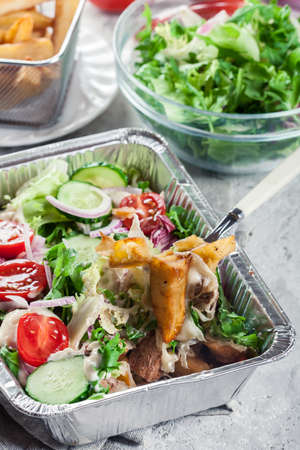 Kapsalon, Dutch fast food witch french fries, chicken tomatoes and cucumber Фото со стока