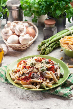 Penne pasta with green asparagus, prosciutto and mushroom in cheese sauce