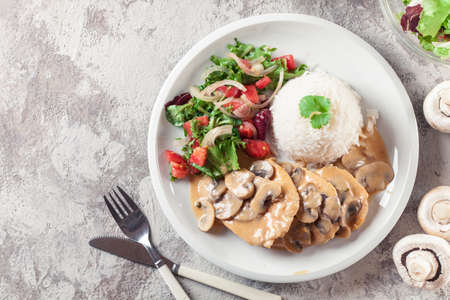 Chicken escalopes with champignion in creamy sauce served with rice Imagens