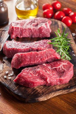 Raw beef steak on a cutting board. Making steak for grilling Фото со стока
