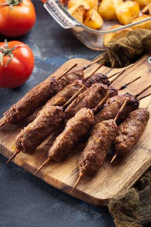 Grilled balkan cevapcici or shish kebab on skewers served on cutting board