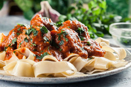 Meatballs with tomato sauce served with pappardelle pasta. Italian cuisine