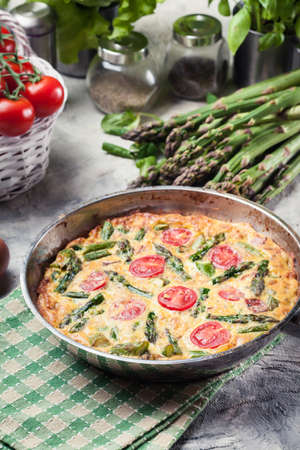 Frittata made of eggs, asparagus and cherry tomatoes on a frying pan. Italian cuisine