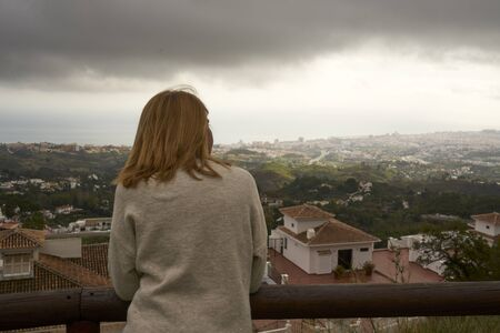blonde woman on her back looking at the horizon on a cloudy day 写真素材