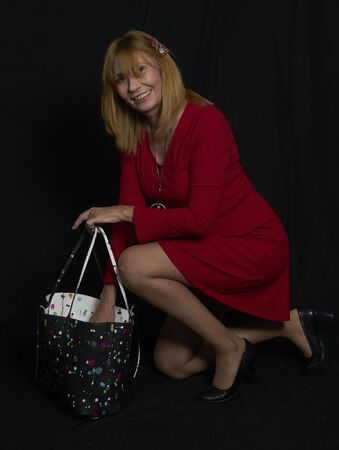 Studio portrait of a beautiful blonde woman with short red dress and accessories with a beautiful smile