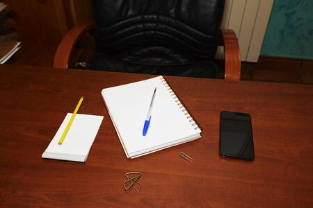 brown desk table with notebook, pens, red scissors, colored pencils