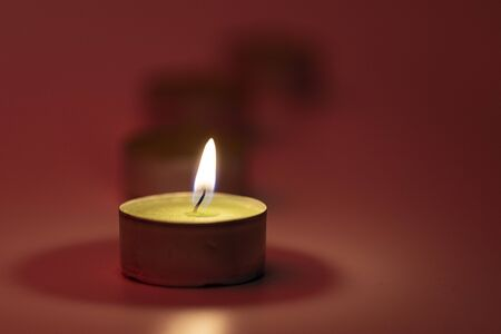 burning candle with blur on red background