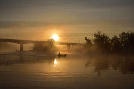 Sunrise, the outline of the bridge in the fog, a mysterious view. Fog.