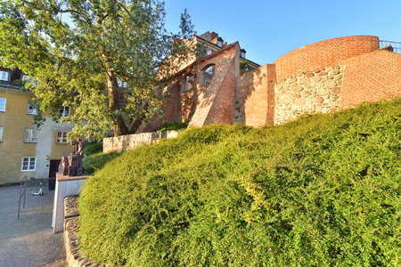 The historic defensive walls of the Warsaw Barbican and burgher houses in the Old Town in the light of the rising sun. Summer.
