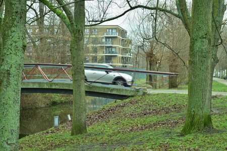A moving car drives over the canal bridge into residential houses and trees. Spring. 免版税图像