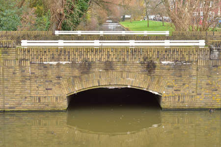 Brick bridge over water in the Netherlands on a gloomy day. Autumn.