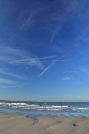 Clouds and traces of airplanes in the blue sky. Spring.