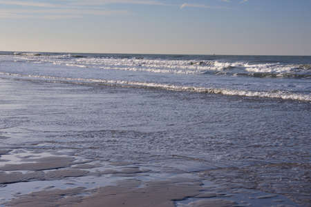 The shore of the sea at low tide, visible sea waves in the distance. Spring. 免版税图像