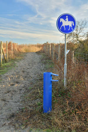 Horse path sign next to the barrier. Afternoon.