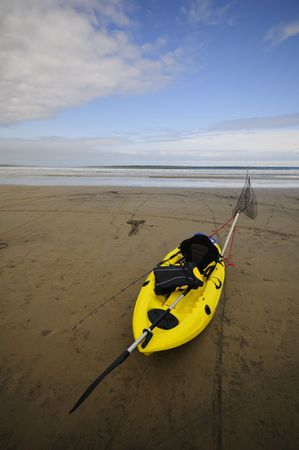 A fishing kayak rests on the beach Stok Fotoğraf