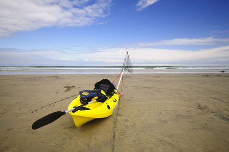 A fishing kayak rests on the beach Stock Photo