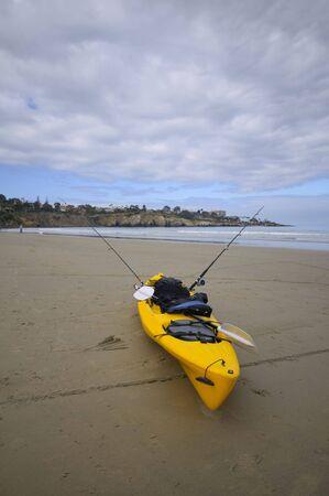 낚시 카약은 해변에 달려있다.