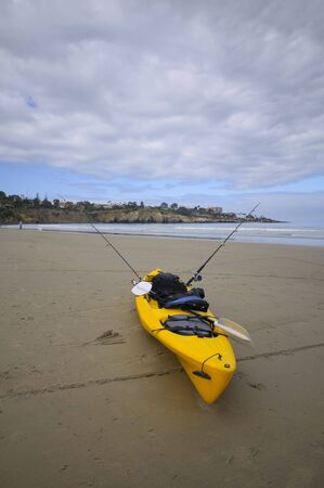 A fishing kayak rests on the beach Imagens