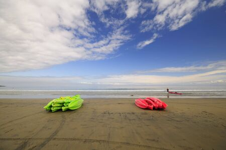 Colorful kayaks lay on the beach