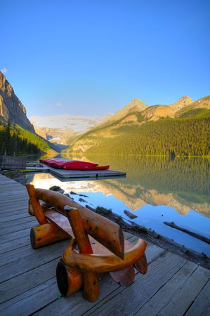 louise: Wooden Chair in the front of Lake Louise, Canada Stock Photo