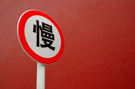 Slow down sign in Chinese with red wall as background