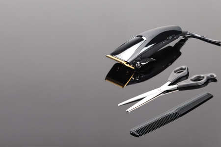 Electric hand-held hair clipper with accessory for hair salon or barber shop on the grey mirror background with copy space