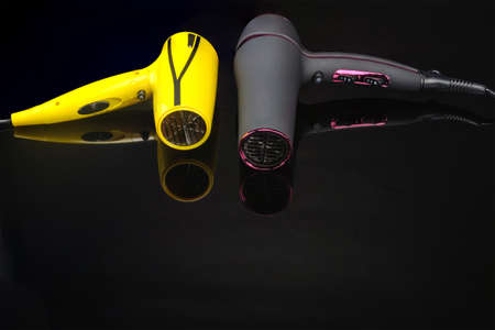 Two electrical hand-held hair dryers for hair salon or barber shop on the black mirror background with copy space Фото со стока