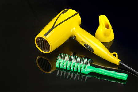 Yellow foldable electrical hand-held hair dryer for hair salon or barber shop on the black mirror background with green comb
