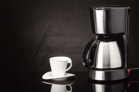Electrical coffee machine with stainless steel coffee pot and cup on the black mirror background