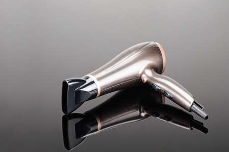 Brown electrical hand-held hair dryer for hair salon or barber shop on the grey mirror background