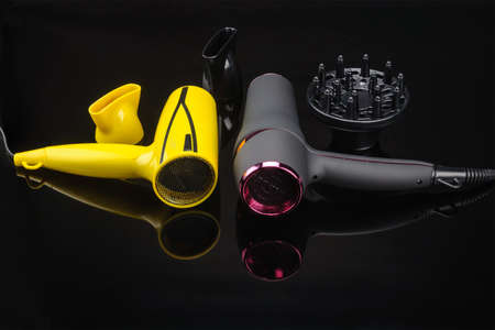 Two electrical hand-held hair dryers for hair salon or barber shop on the black mirror background with accessory