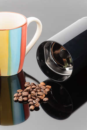 Black coffee grinder with handful coffe beans and mug on the grey mirror background