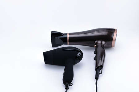 Two electrical hand-held hair dryers for hair salon or barber shop on the white background with copy space. Фото со стока