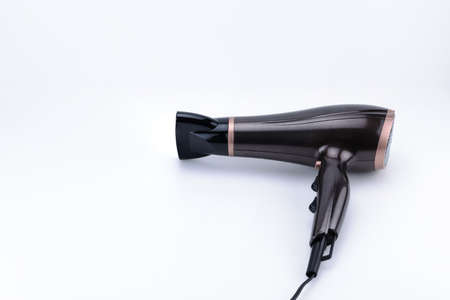 Brown glossy electrical hand-held hair dryer for hair salon or barber shop on the white background with copy space. Фото со стока