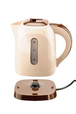 Bollitore elettrico cordless in plastica di colore beige e marrone con base isolata sullo sfondo bianco