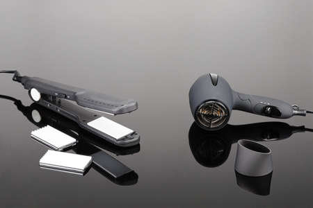 Grey mat electrical hand-held hair iron and grey dryer for hair salon or barber shop on the grey mirror background